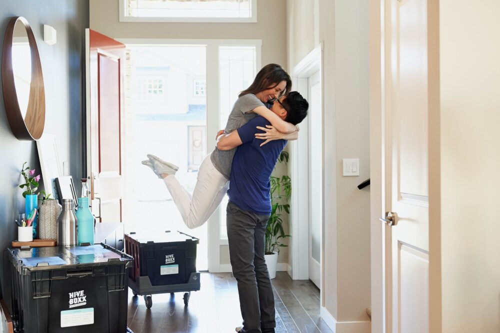 couple embrace in hallway of their new home first time buying